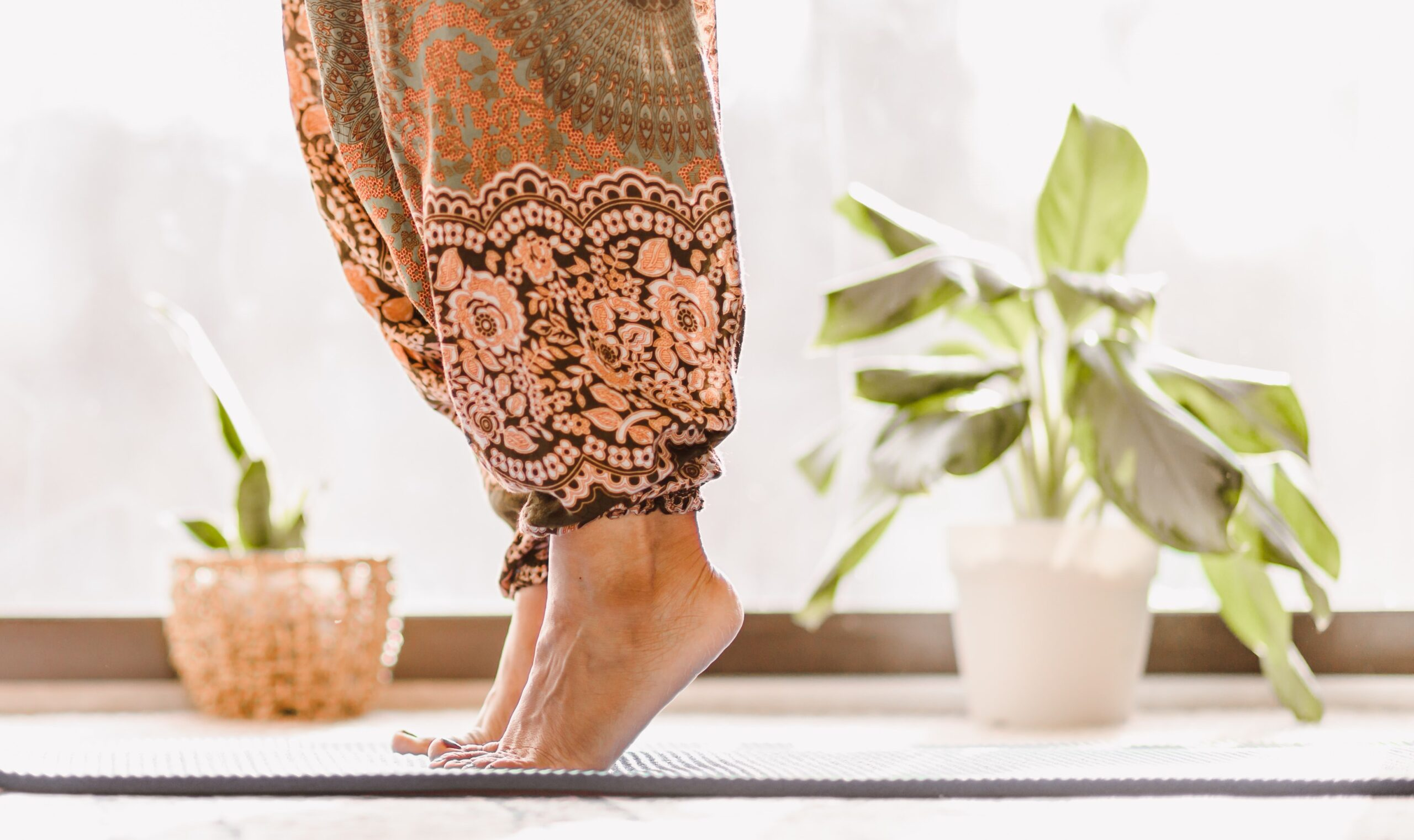 A person standing on their tip toes on a yoga mat